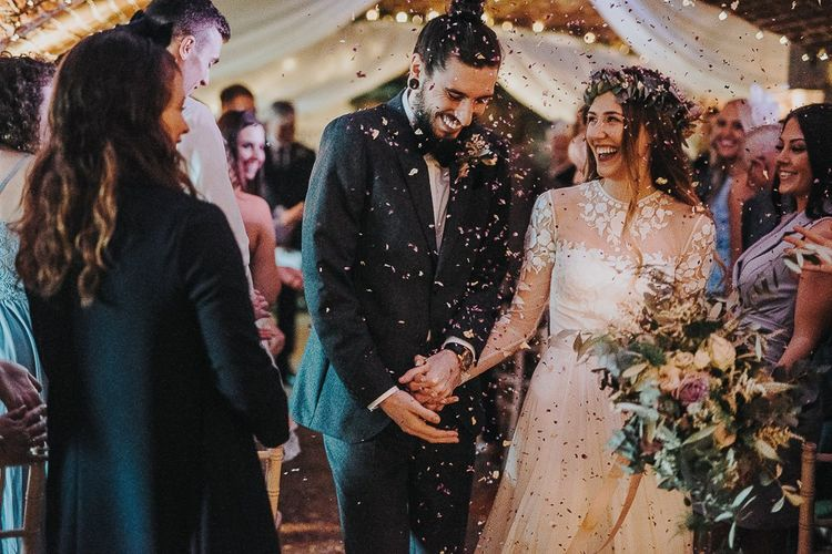 Confetti Moment with Bride in Catherine Deane Jessica Bodysuit and Anika Skirt Separates  and Groom in Tuxedo Walking Up the Altar