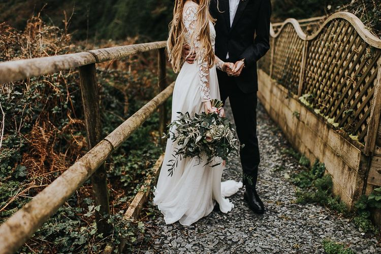 Bride in Catherine Deane Separates with Long Sleeves Holding a Wildflower Bouquet