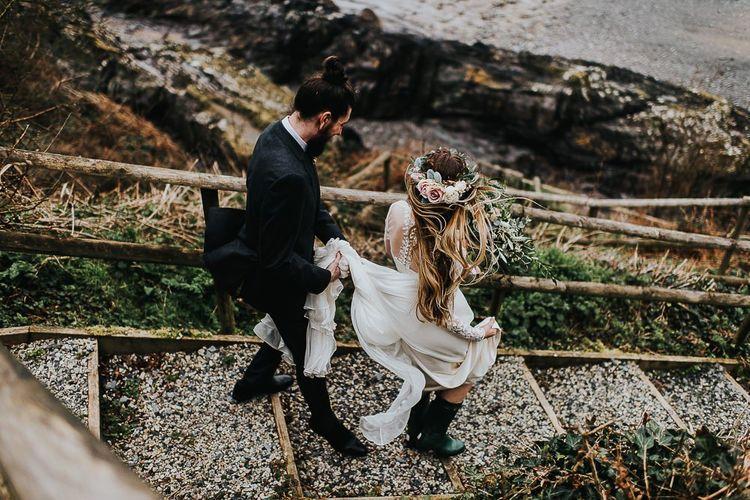 Groom Holding His Brides Wedding Dress Train Walking to the Beach