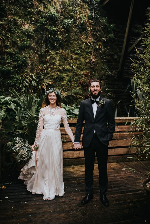 Stylish Bride in Catherine Deane Separates and Flower Crown and Groom in Tuxedo  Holding Hands