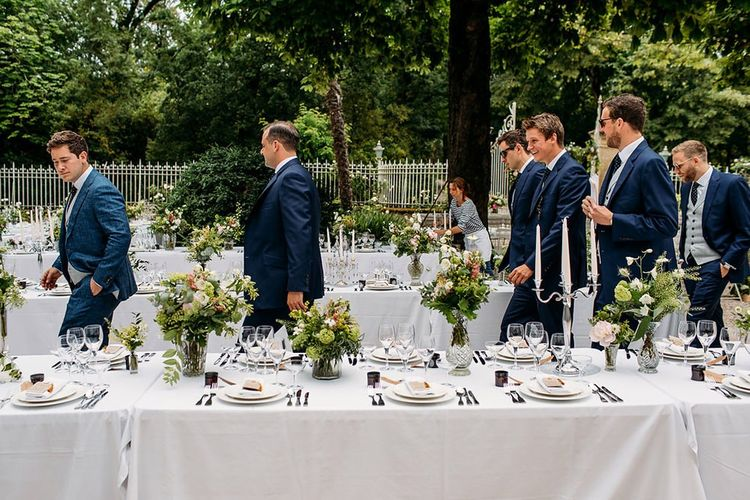 Groomsmen in Navy Suit Walking Through the  White and Green  Decorated Outdoor Reception