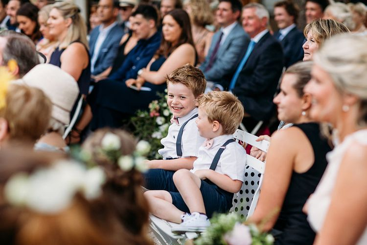 Page Boys in Shorts, Braces and Bow Ties Giggling During The Wedding Ceremony