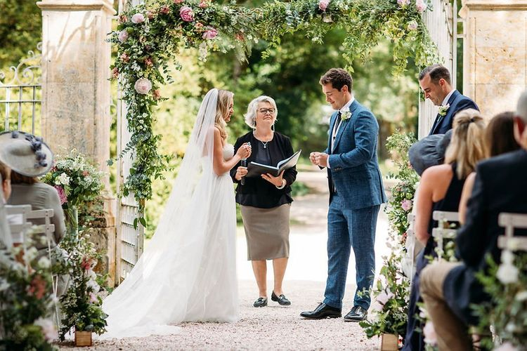 Outdoor Wedding Ceremony with Pink and Green Floral Arch