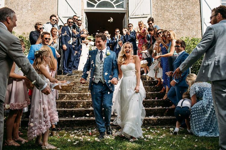 Confetti Exit with Bride in Strapless Pronovias Wedding Dress and Groom in Blue Suit