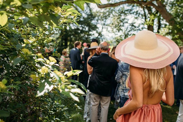 Stylish Wedding Guest in Backless Dress and Giant Straw Hat