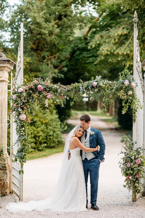 Bride in Pronovias Wedding Dress and Groom in Navy Suit Supply Suit Embracing at  Chateau Lartigolle Gates