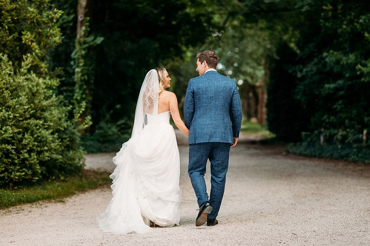 Bride in Pronovias Wedding Dress and Groom in Navy Suit Supply Suit Holding Hands