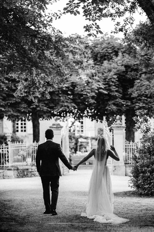 Black and White Portrait of Bride in Pronovias Wedding Dress and Groom in Navy Suit Supply Suit Holding Hands