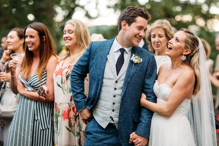 Bride in Sweetheart Neckline Wedding Dress and Groom in Blue & Grey Suit Laughing During the Outdoor Wedding Speeches