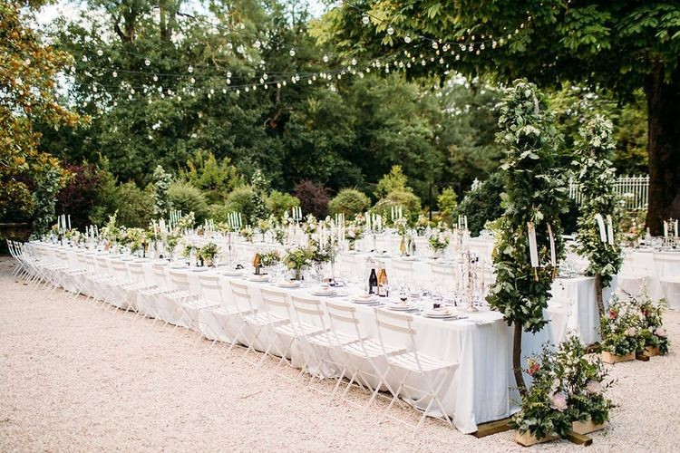 Outdoor Wedding Breakfast with Long Tables Decorated with White and Green Flowers and Candelabras