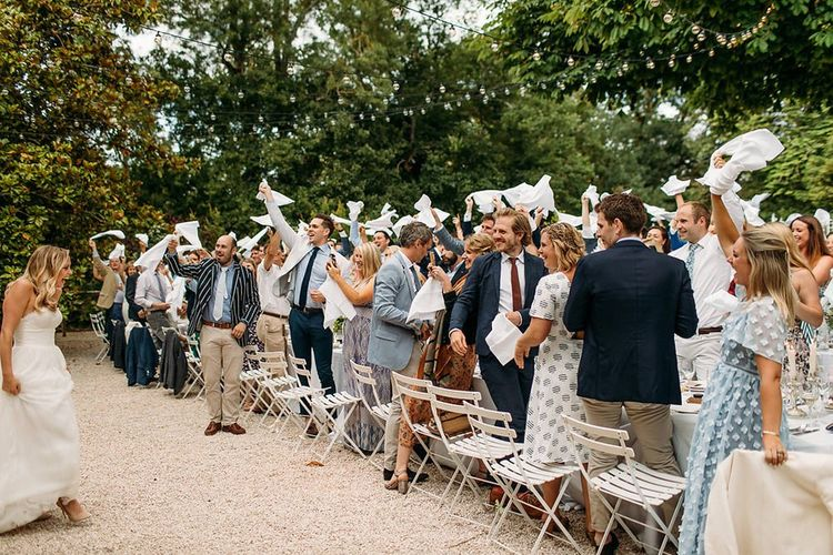 Wedding Guests Waving Their Napkins as the Bride and Groom Arrive for the Outdoor Wedding Reception