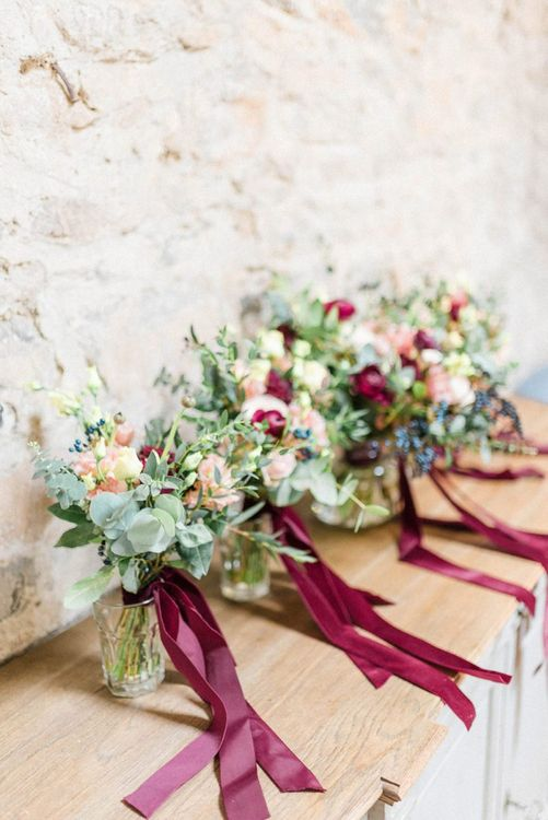 February wedding bouquets tied with burgundy ribbon