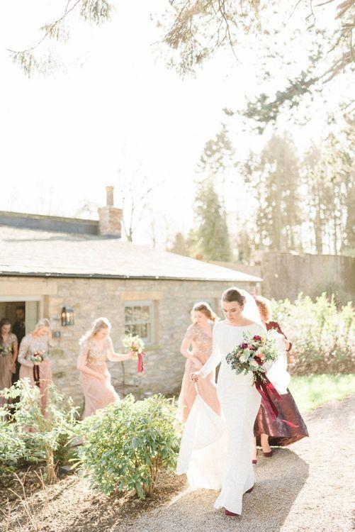 Bride in Justin Alexander wedding dress walking to her February wedding ceremony