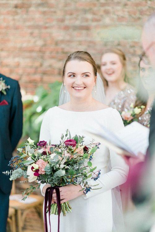 Bride in long sleeve wedding dress holding a winter wedding bouquet