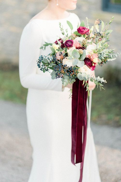 Winter wedding bouquet with berries, foliage and deep red flowers tied with velvet ribbon