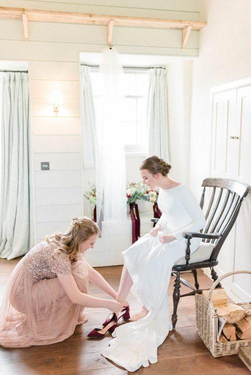 Bride in long sleeve dress putting on burgundy wedding shoes