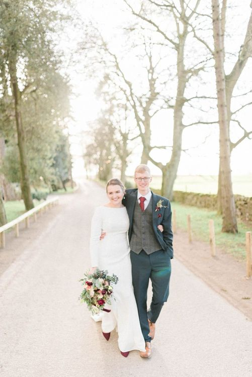 Groom embracing his bride in along sleeve wedding dress