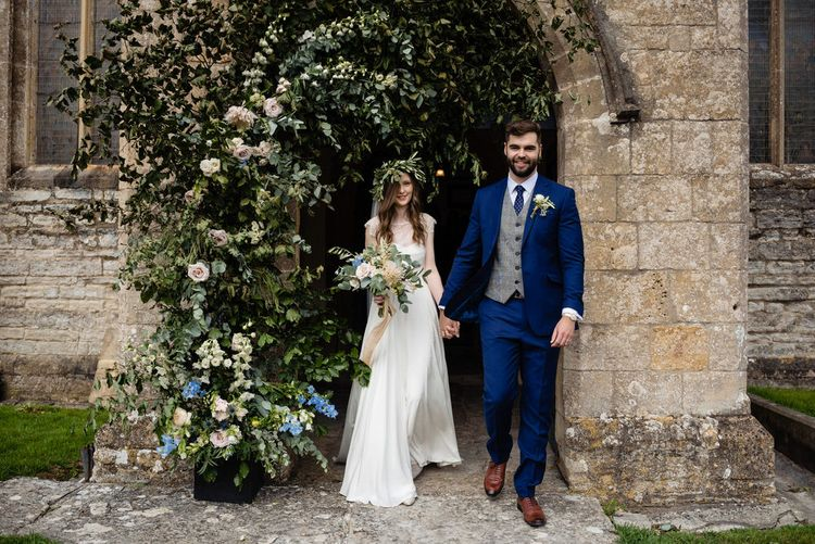 Bride in Charlie Brear Wedding Dress and Groom in Navy Ted Baker Suit Exiting the Church Decorated with Flowers