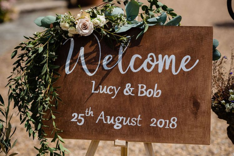 Wooden Wedding Welcome Sign with White Calligraphy Writing and Flower Decor