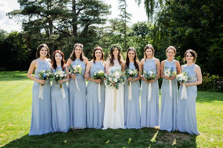 Bridal Party with Bridesmaids in Blue Monsoon Dress and Bride in Charlie Brear Wedding Dress Holding Pastel Flower Bouquets