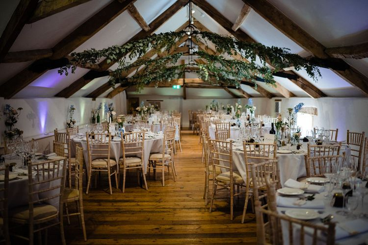 Pennard House Wedding Reception Decor with Beams Covered in Foliage and Pastel Wedding Flower Stems in Bottles as Centrepieces