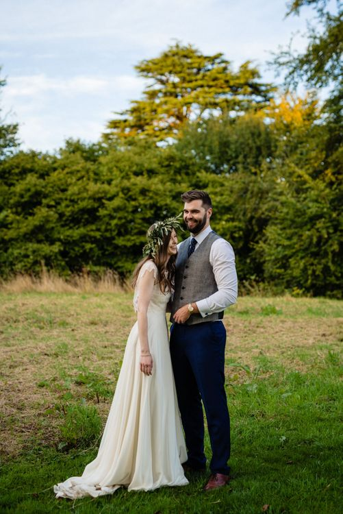 Bride in Charlie Brear Wedding Dress and Olive Flower Crown with Groom in Ted Baker Navy Suit Laughing