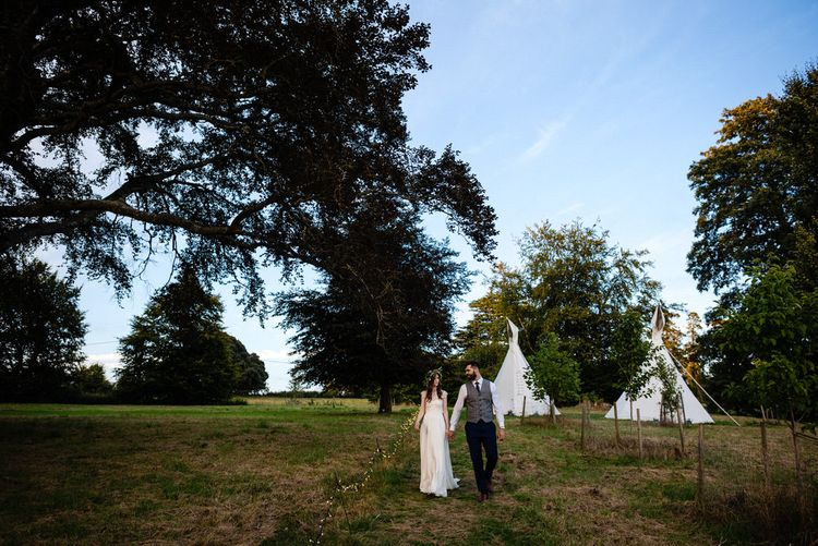 Bride in Charlie Brear Wedding Dress and Olive Flower Crown with Groom in Ted Baker Navy Suit Holding Hands Walking Through Glamping Field