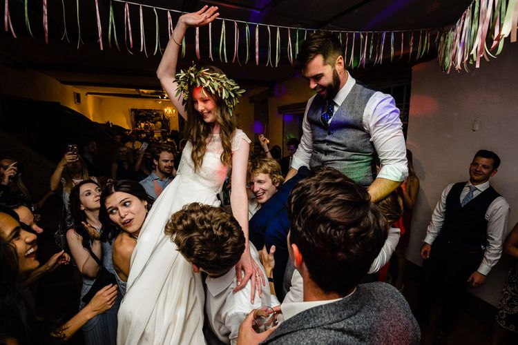 Bride in Charlie Brear Wedding Dress and Olive Flower Crown with Groom in Ted Baker Navy Suit Being Held up on the Dance  Floor