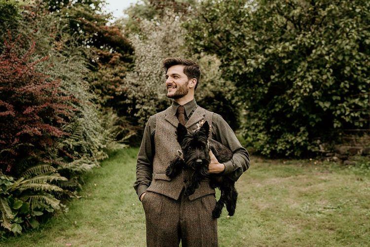 Groom in tweed waistcoat with pet dog for September wedding