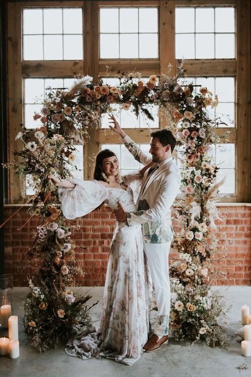 Bride and Groom Celebrating in Front of Dried Flower Wedding Arch