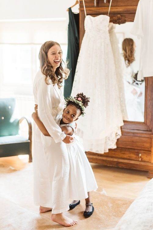 Wedding Morning Bridal Preparations with Bride in Getting Ready Robe Hugging Flower Girl