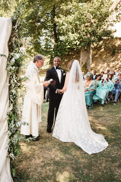 Outdoor Wedding Ceremony at at Chateau de Lartigolle with Bride in Jesus Peiro Wedding Dress and Groom in Ralph Lauren Purple Label Tuxedo