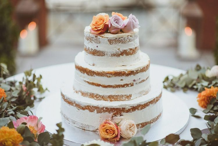 Semi naked wedding cake decorated with fresh flowers