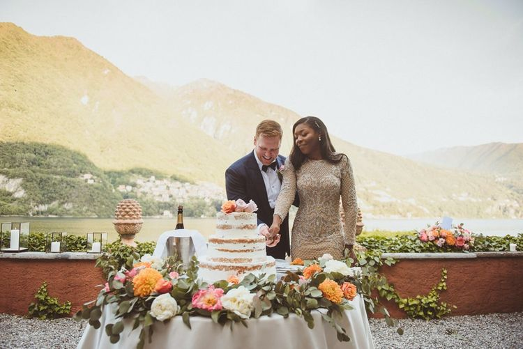 Bride and groom cutting the cake outside at Lake Como wedding