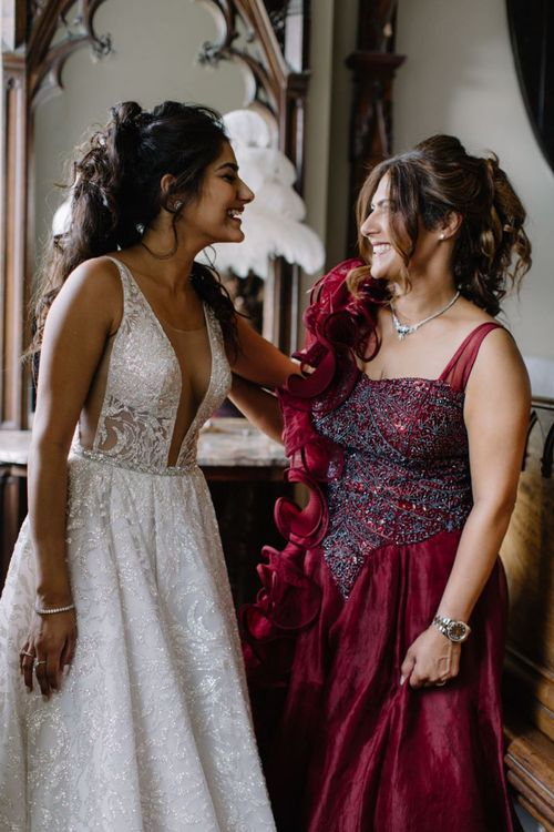 Bride in Berta Bridal gown with friend in red ball gown
