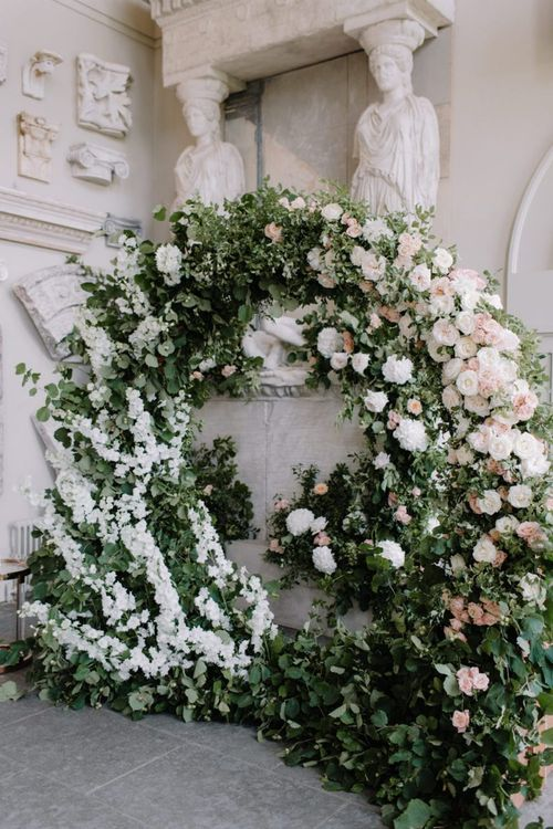 Green, white and pink floral moon gate at Aynhoe Park