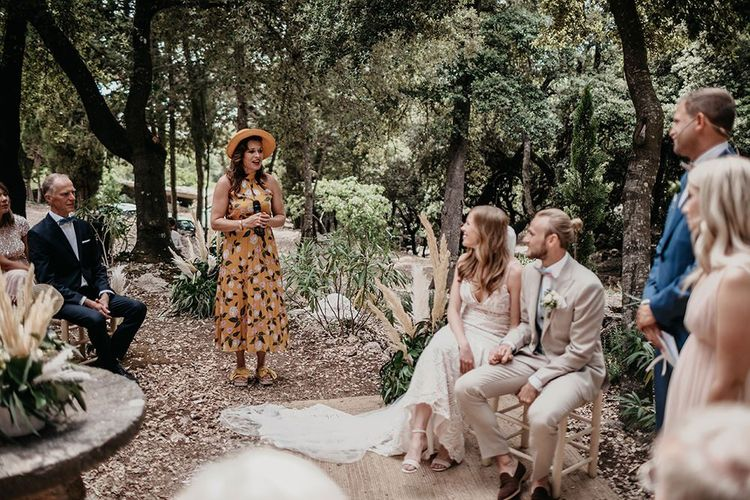 Bride and groom in beige wedding suit during forest ceremony