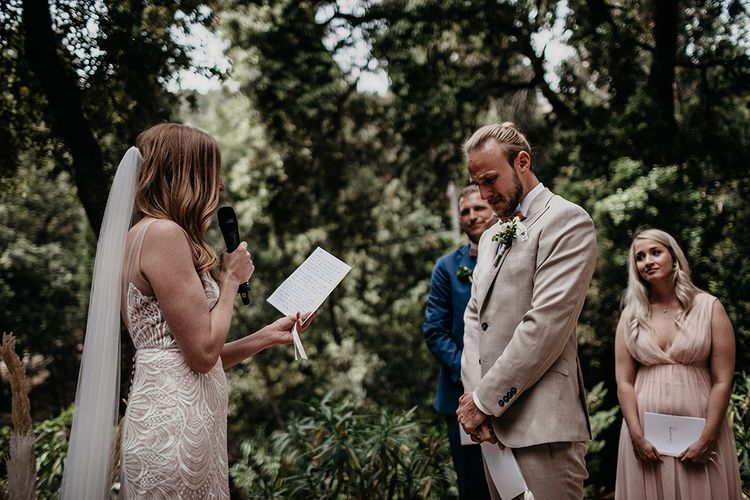 Emotional ceremony as bride reads vows and groom in beige wedding suit listens