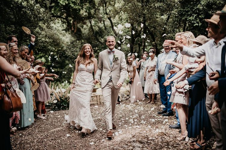 Confetti exit for bride in Made With Love thing strapped dress and groom in beige wedding suit