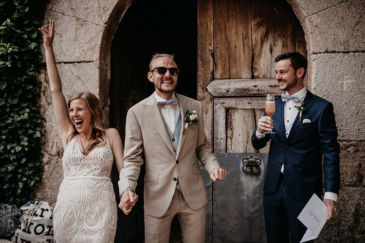 Bride and groom in beige wedding suit make entrance to reception