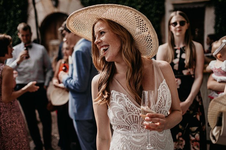 Bride in straw hat and Made With Love wedding dress