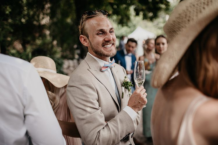 Groom in beige wedding suit with blue waistcoat and bowtie