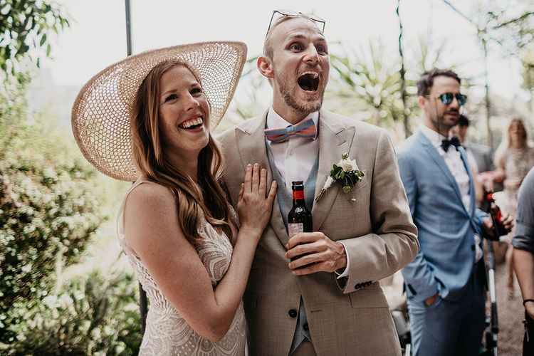 Groom in beige wedding suit with blue waistcoat and bowtie with bride in straw hat