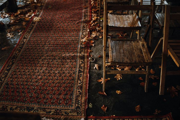 Persian Rugs and Autumn Leaves Lining Aisle | Rustic Wooden Chairs | Mariachi Band and Persian Rug Aisle for Autumn Wedding | Leah Lombardi Weddings