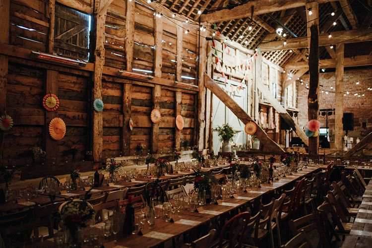 Wooden Banquet Tables | Mismatched Rustic Chairs | Paper Fans | Festoon Lights | Bunting | Kraft Place Settings | Pink, Orange and Maroon Flowers for Tables | Mariachi Band and Persian Rug Aisle for Autumn Wedding | Leah Lombardi Weddings