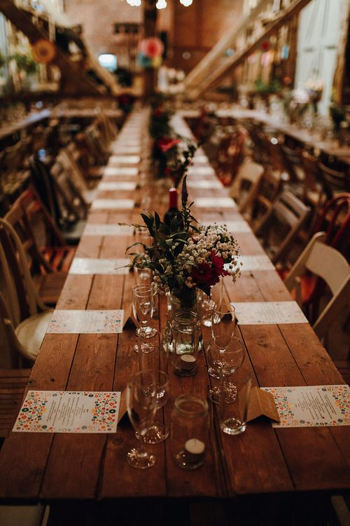 Wooden Banquet Tables | Mismatched Rustic Chairs | Tea Lights in Jars | Kraft Place Settings | Wedding Breakfast Menus | Red and White Flowers and Foliage Centrepieces | Mariachi Band and Persian Rug Aisle for Autumn Wedding | Leah Lombardi Weddings
