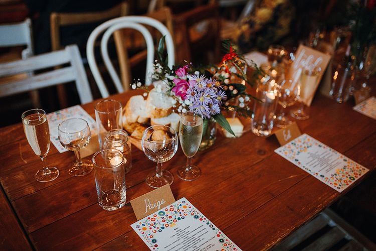Wooden Banquet Tables | Mismatched Rustic Chairs | Tea Lights in Jars | Kraft Place Settings | Wedding Breakfast Menus | Purple and Pink Table Flowers | Mariachi Band and Persian Rug Aisle for Autumn Wedding | Leah Lombardi Weddings