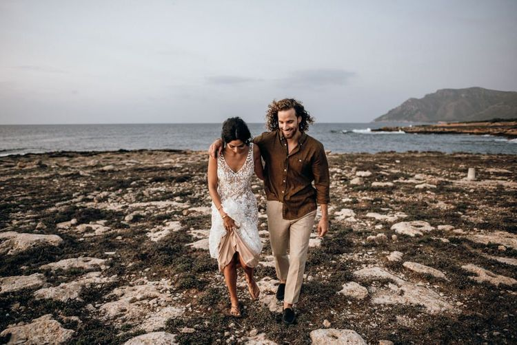 Bride and groom walking on the rocks at Mallorca elopement