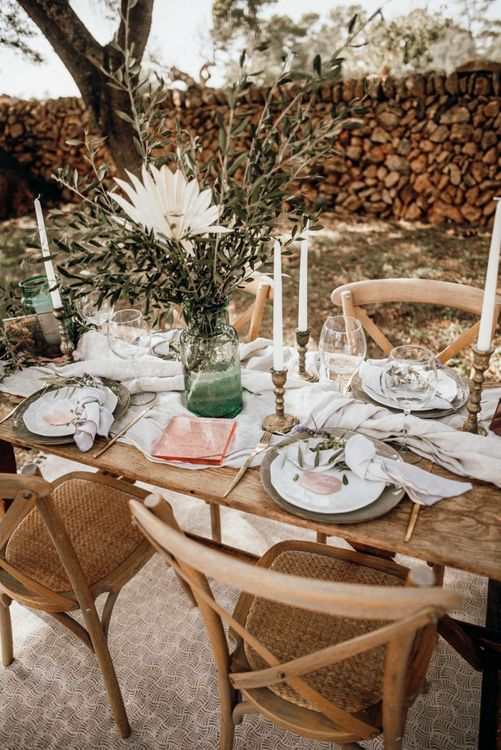 Mallorca elopement table decor with white linens, gold candles, foliage and pink stationery