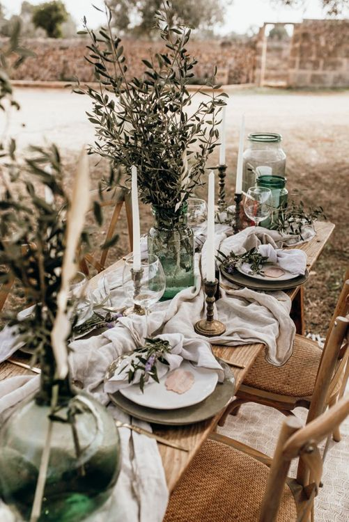wedding table decor with gold candlesticks, linens and foliage
